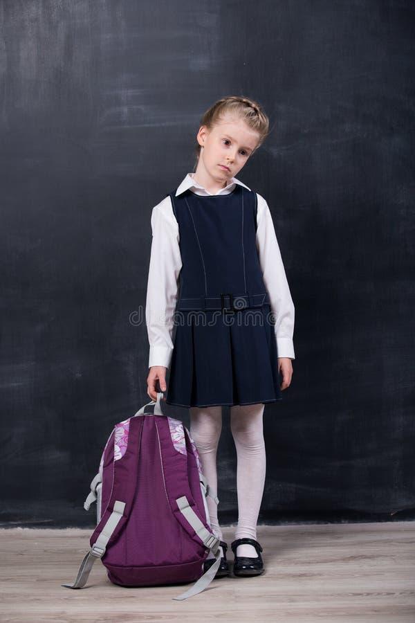 Piccola scolara con lo zaino vicino alla lavagna fotografie stock libere da diritti