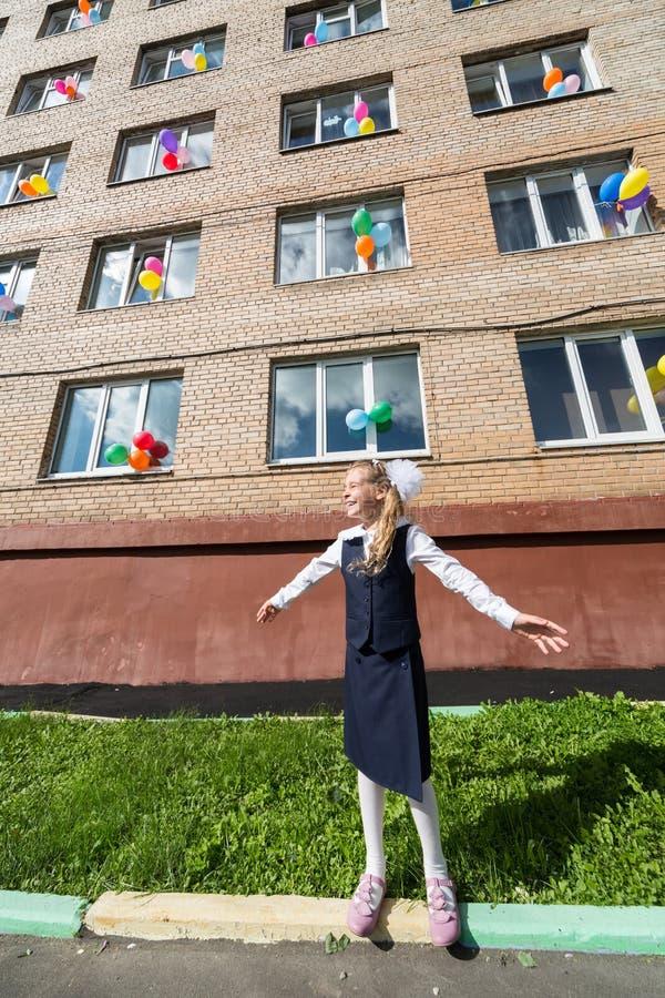 Piccola scolara davanti alla scuola immagine stock