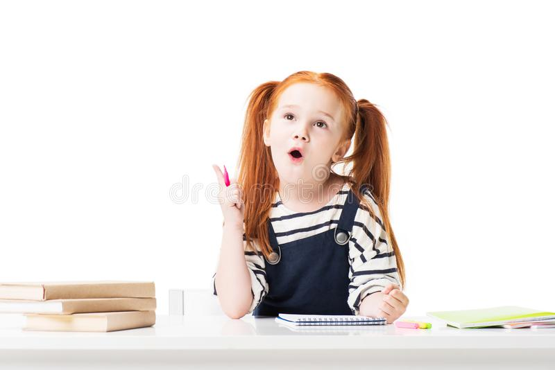 piccola scolara sorpresa che assorbe taccuino e cercare fotografia stock