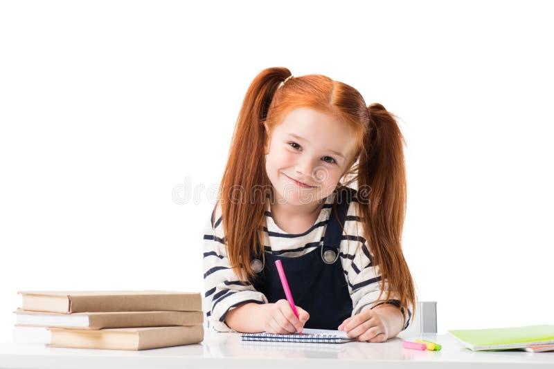 piccola scolara sorridente della testarossa che assorbe taccuino con i pennarelli ed esame della macchina fotografica immagine stock libera da diritti