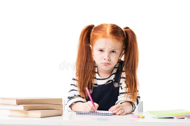 piccola scolara turbata che assorbe taccuino con i pennarelli e che esamina macchina fotografica fotografia stock