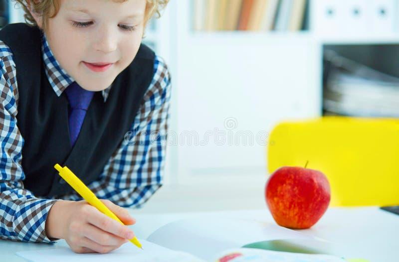 Piccola scrittura caucasica dello scolaro in un taccuino che si siede ad una tavola La mela rossa si trova accanto alla tavola Te fotografia stock libera da diritti