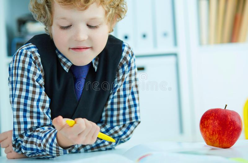 Piccola scrittura caucasica dello scolaro in un taccuino che si siede ad una tavola La mela rossa si trova accanto alla tavola Te fotografia stock