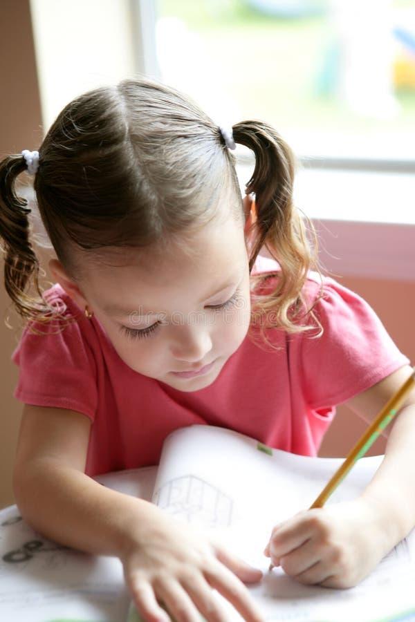 Piccola scrittura della ragazza del bambino allo scrittorio del banco immagini stock libere da diritti
