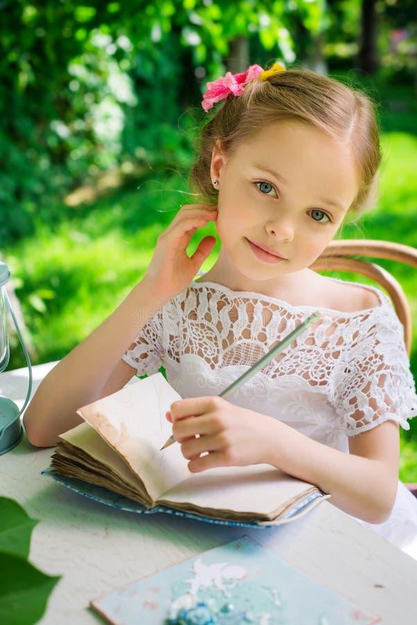 Piccola scrittura sorridente della ragazza sul taccuino all'aperto nel parco vi fotografia stock libera da diritti