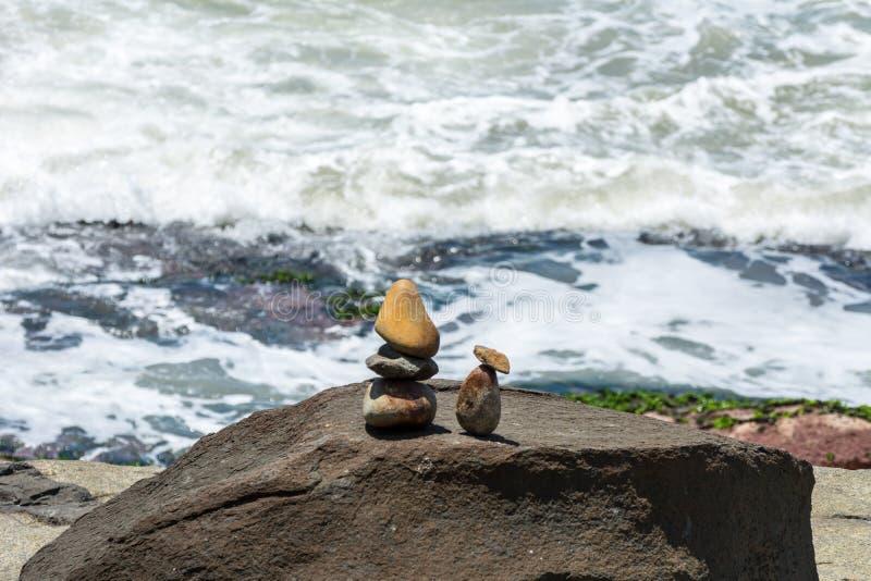 Piccola scultura due persone di somiglianza delle pietre davanti al mare, su una regione rocciosa, in Florianopolis, il Brasile immagine stock libera da diritti