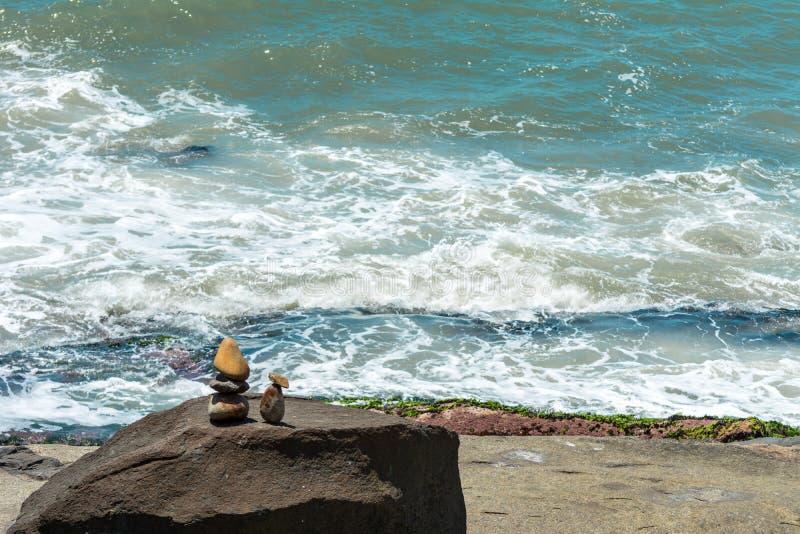 Piccola scultura due persone di somiglianza delle pietre davanti al mare, su una regione rocciosa, in Florianopolis, il Brasile fotografie stock