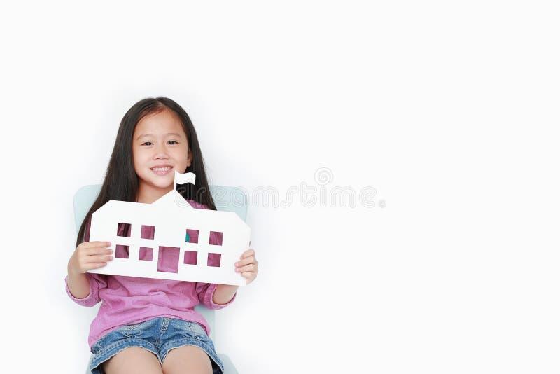 Piccola scuola asiatica sorridente della carta del modello della tenuta della ragazza del bambino che si siede sulla sedia del ba fotografie stock