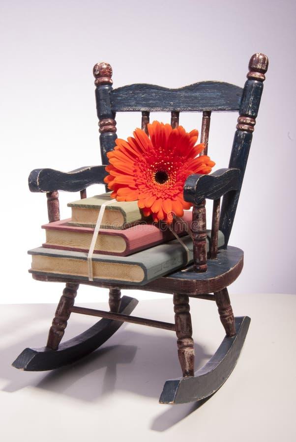 Piccola sedia di oscillazione con i libri ed il fiore fotografie stock libere da diritti