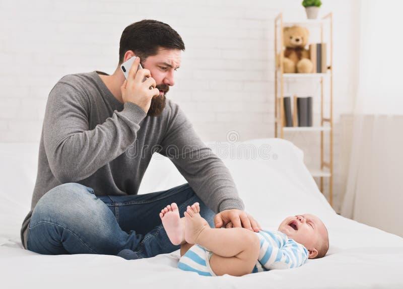 Piccola sofferenza babby dalla colica, papà che chiama per aggiustare immagini stock