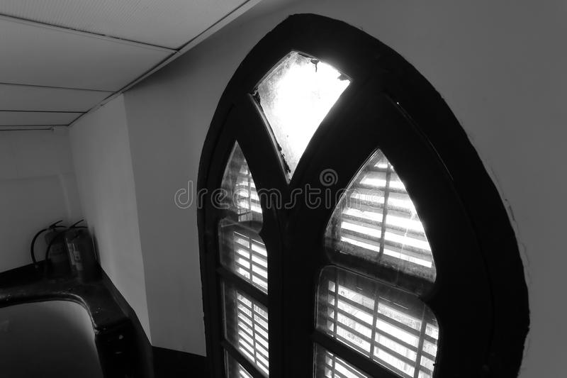 Piccola soffitta di stile europeo con l'immagine in bianco e nero incurvata della finestra immagini stock