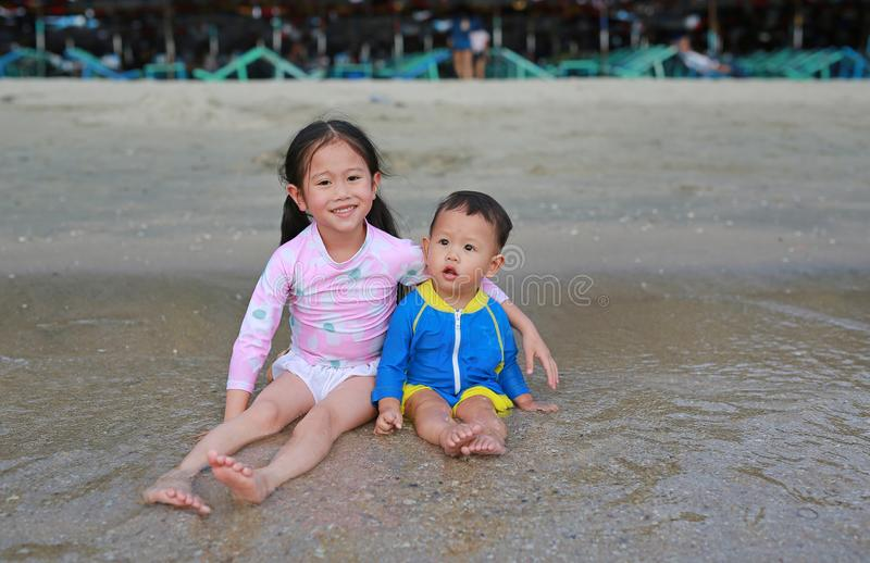 Piccola sorella asiatica adorabile ed suo fratello piccolo in vestito di nuoto che si siede e che gioca le onde del mare sulla sp immagine stock