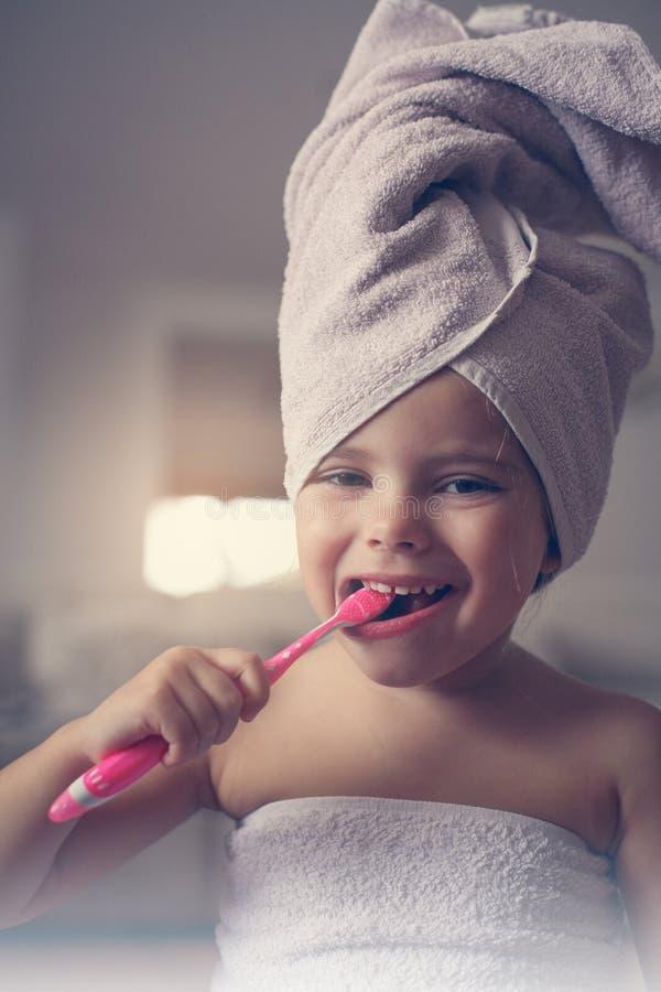 Piccola spazzola caucasica della ragazza i suoi denti nel bagno immagine stock libera da diritti