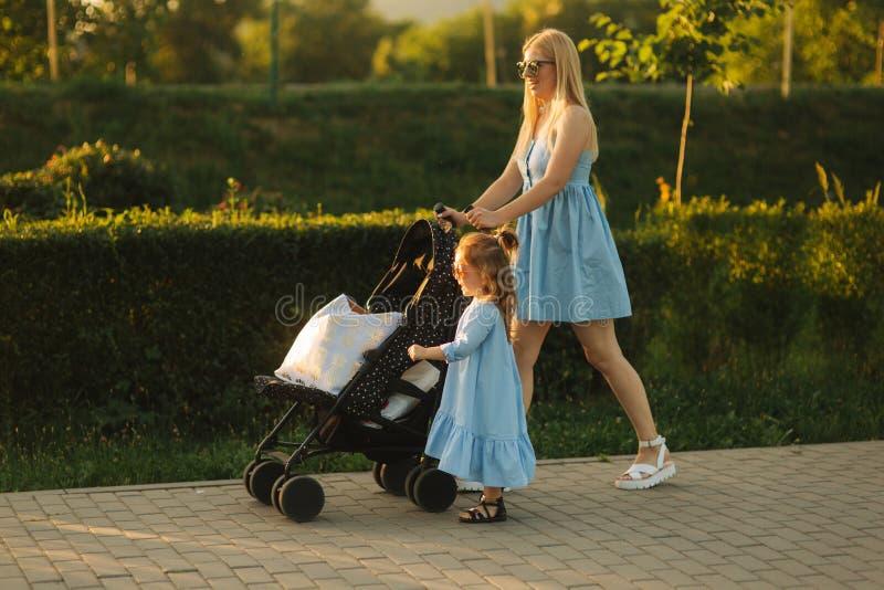 Piccola spinta della mamma di aiuti della figlia la carrozzina Famiglia felice immagine stock libera da diritti