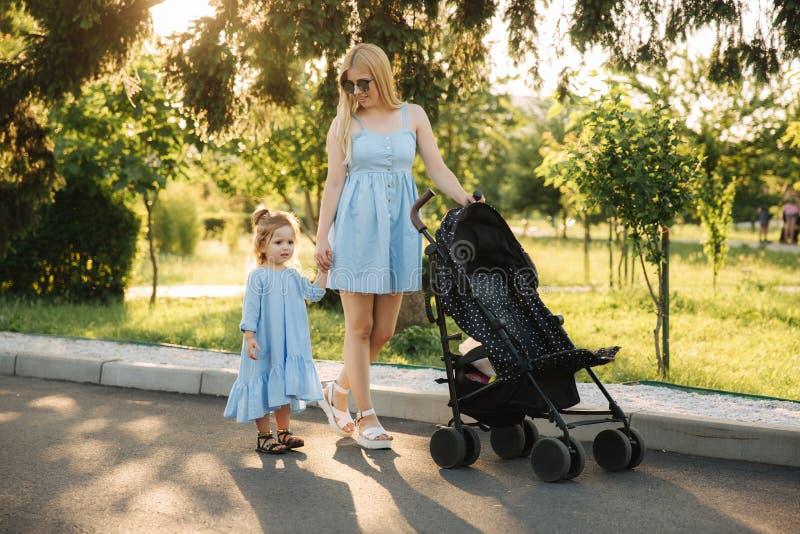 Piccola spinta della mamma di aiuti della figlia la carrozzina immagine stock