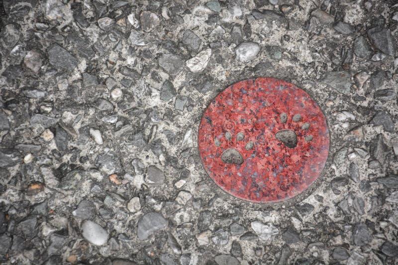 Piccola stampa della zampa del gatto sul cerchio mable rosso con il fondo di pietra della pavimentazione della ghiaia situato nel fotografia stock