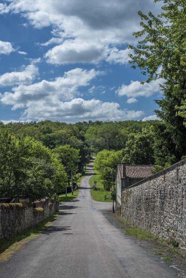 Piccola strada che conduce un villaggio francese alla foresta immagini stock
