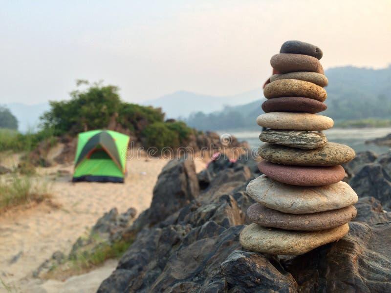 Piccola torre della pietra di zen con il campeggio fotografia stock