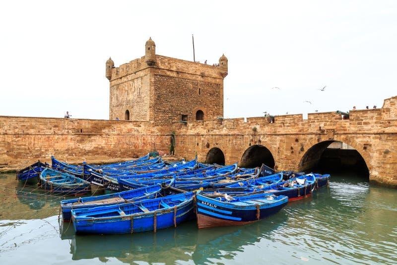 Piccole barche blu nel porto di Essaouira con la fortezza immagine stock libera da diritti