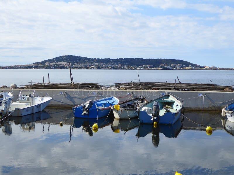Piccole barche nella città di trascuratezza del pendio di collina del porto immagini stock libere da diritti