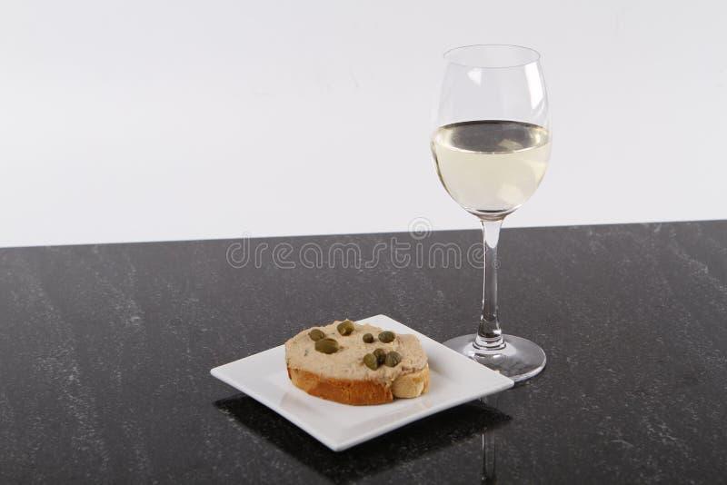 Piccole canape con il tonno e capperi e un vetro di champagne immagine stock