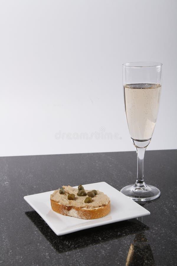 Piccole canape con il tonno e capperi e un vetro di champagne fotografia stock libera da diritti