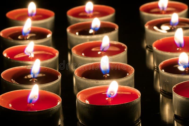 Piccole candele rosse in ciotole del metallo che bruciano nello scuro fotografia stock libera da diritti