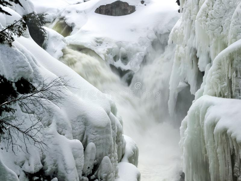 Piccole cascate che precipitano a cascata nel fiume stretto con le banche coperte in neve e ghiacciolo fotografia stock