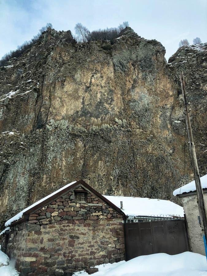 Piccole case di pietra, costruzioni nel villaggio su una localit? di soggiorno fredda di inverno della bella montagna con la fosc immagini stock libere da diritti