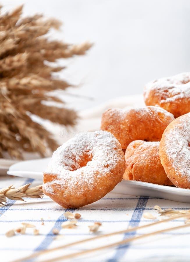 Piccole ciambelle cosparse di zucchero in polvere Su un piatto bianco In fondo, le orecchie e i chicchi di frumento fotografia stock