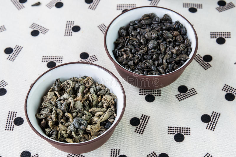 Piccole ciotole di foglie di tè verdi asciutte fotografia stock