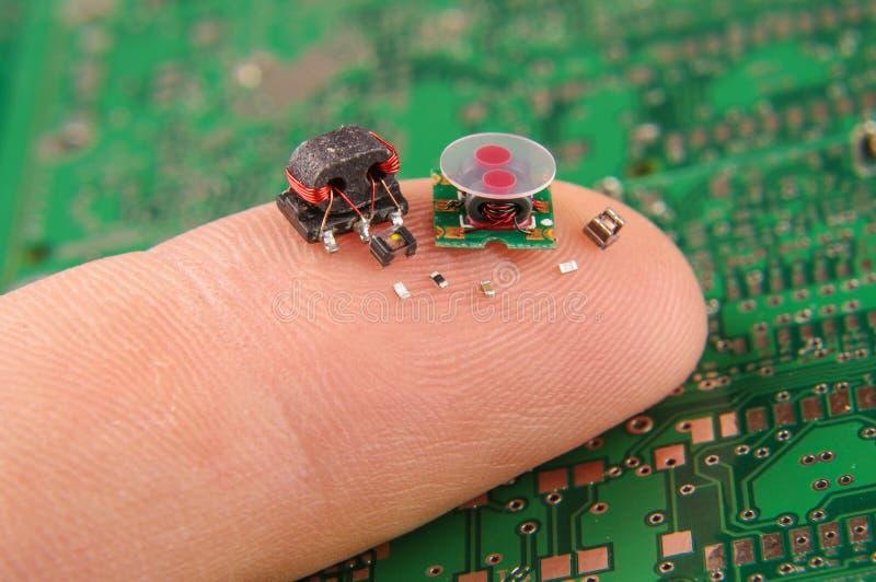 Piccole componenti di elettronica sul dito umano immagini stock libere da diritti