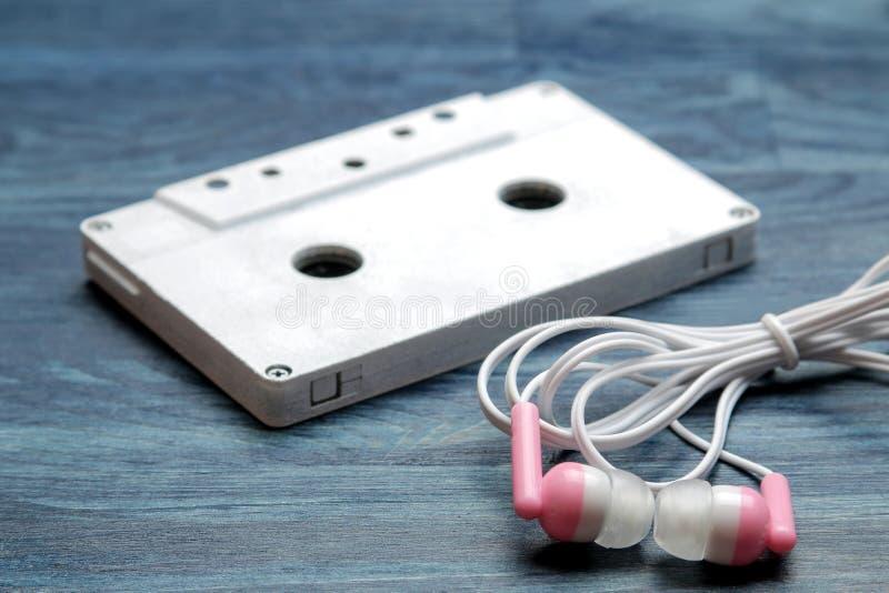 Piccole cuffie rosa ed audio cassetta su un fondo di legno blu scuro Primo piano fotografia stock