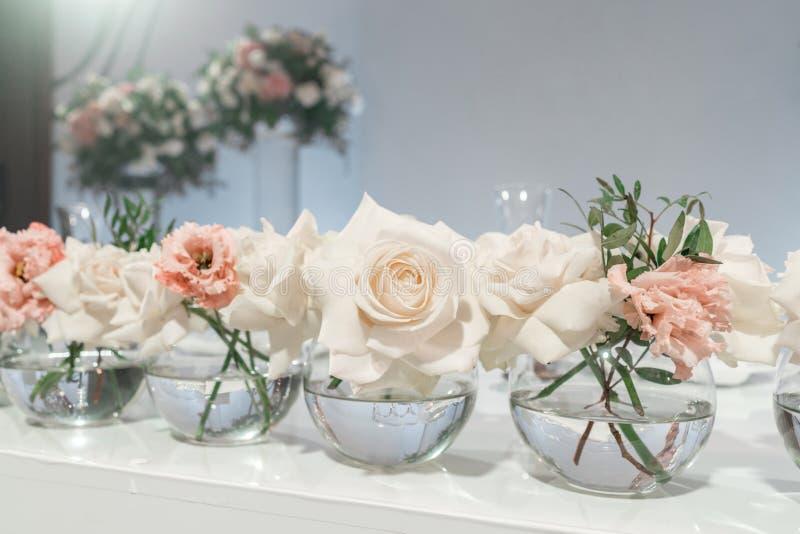 Piccole disposizioni dei fiori in vasi di vetro della palla La tavola delle persone appena sposate Interno del ristorante per la  fotografia stock libera da diritti