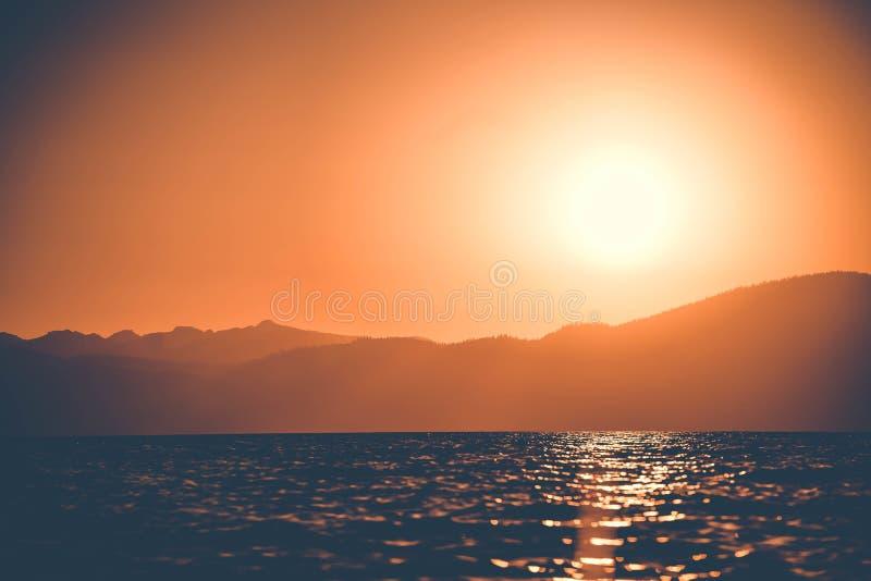 Piccole onde del lago Tahoe, CA che riflette il bello tramonto con la montagna nei precedenti fotografie stock libere da diritti