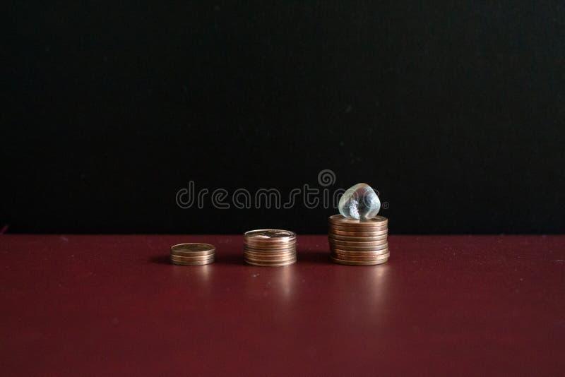 3 piccole pile di euro monete dei soldi e di pietra preziosa di cristallo fotografia stock