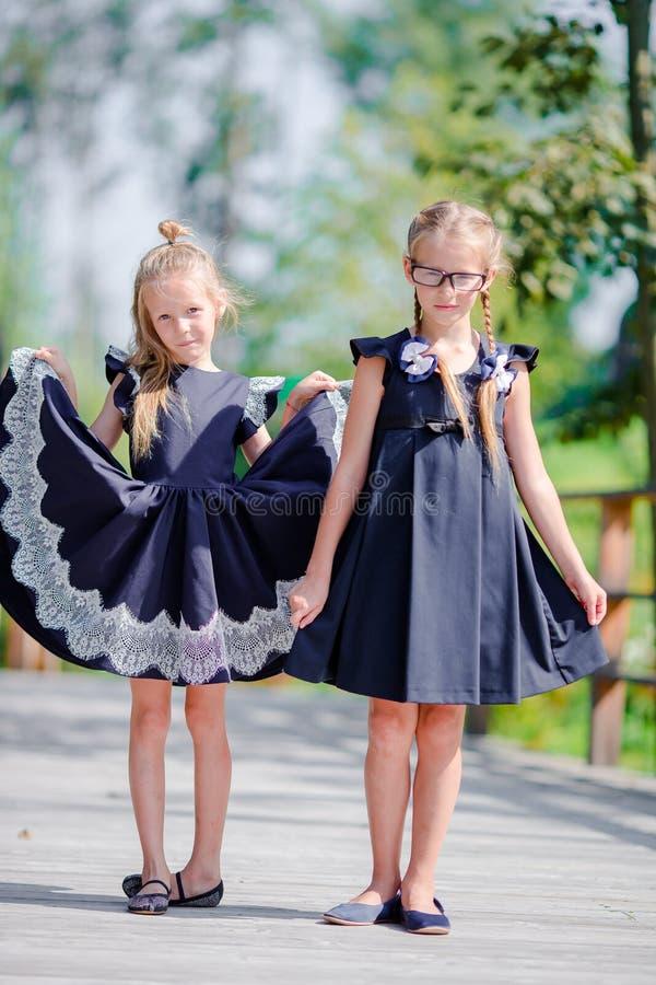 Piccole ragazze adorabili della scuola all'aperto nel giorno caldo di settembre Di nuovo al banco fotografie stock libere da diritti