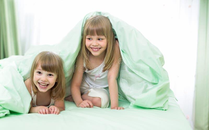 Piccole ragazze felici che si trovano sotto la coperta sul letto fotografia stock immagine di - Foto di donne sul letto ...