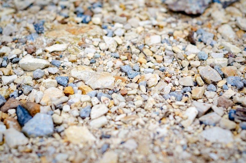 Piccole rocce sulla strada boscosa in natura vicino ad un fiume immagine stock libera da diritti