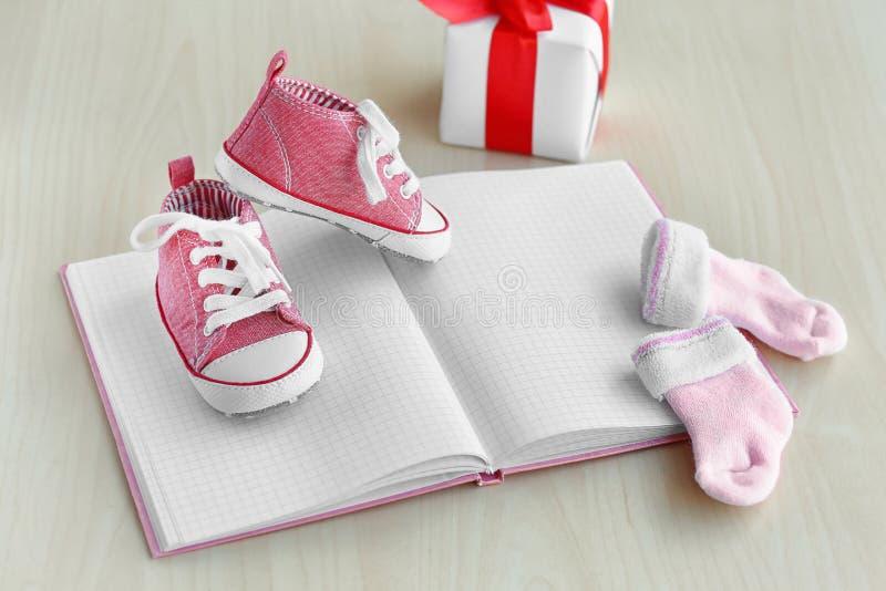 Piccole scarpe di bambino, taccuino, calzini e scatola attuale su fondo di legno immagini stock libere da diritti
