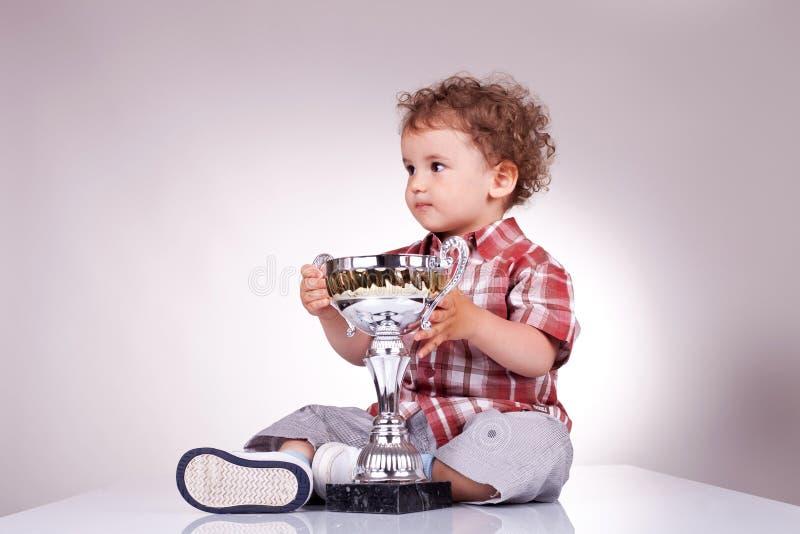 Piccole seduta e holding del ragazzo un trofeo immagini stock