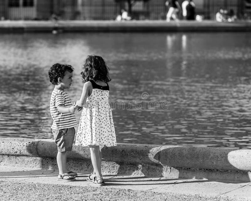 Piccoli amici ragazza e ragazzo che giocano nei giardini del Lussemburgo P fotografia stock