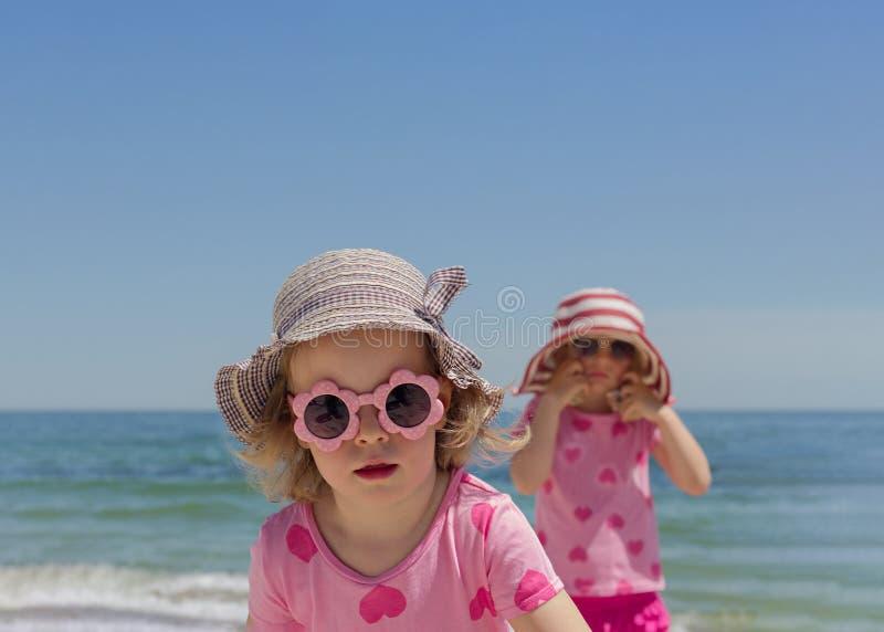 Piccoli anni divertenti delle ragazze 3 e 4 delle sorelle al wearin del mare immagine stock libera da diritti