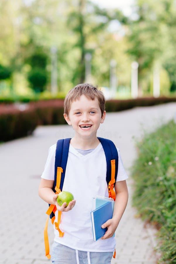 Piccoli 7 anni felici del ragazzo al suo primo giorno alla scuola immagine stock libera da diritti