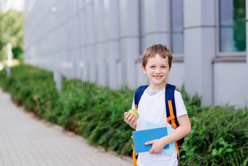 Piccoli 7 anni felici del ragazzo al suo primo giorno alla scuola fotografia stock