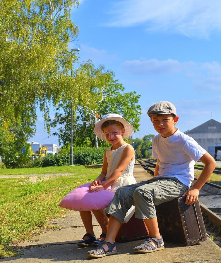 Piccoli bambini adorabili su una stazione ferroviaria, aspettante il treno con le valigie d'annata Conce di viaggio, di festa e d fotografia stock