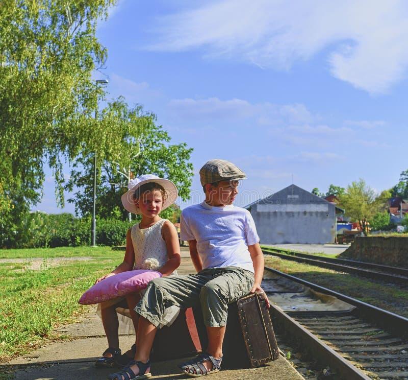 Piccoli bambini adorabili su una stazione ferroviaria, aspettante il treno con le valigie d'annata Conce di viaggio, di festa e d fotografie stock libere da diritti