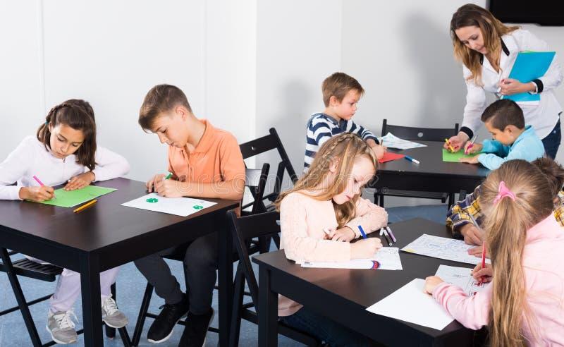 Piccoli bambini attenti con l'insegnante che assorbe aula immagine stock