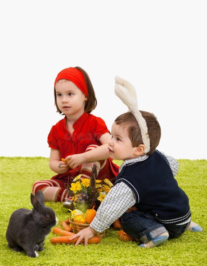 Piccoli bambini che giocano con il coniglietto di pasqua fotografia stock
