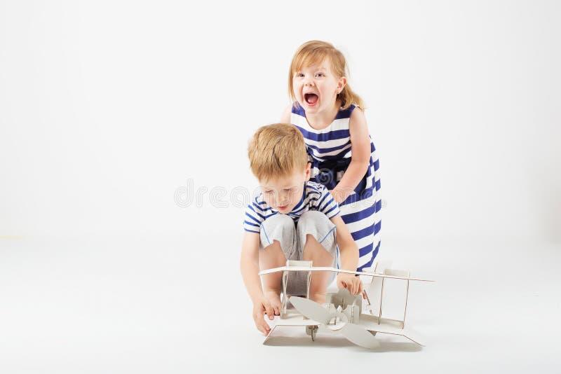 Piccoli bambini che giocano con l'aeroplano di carta del giocattolo che si siede sulla f immagini stock libere da diritti
